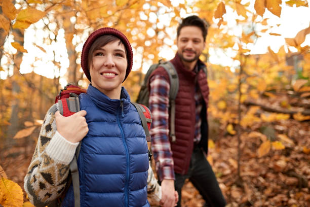 Attractive caucasian couple hiking through the forest in the fall in Canada stock photo