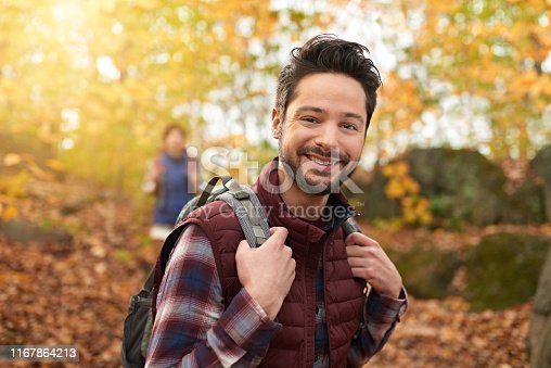 Portait of an attractive millennial man walking in autumn nature with his girlfriend and trekking on a path surrounded by orange leaves