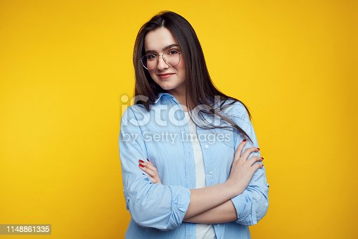 Cheerful young good looking woman with clean skin posing indoors with crossed arms, smiling broadly with her white straight teeth, wearing blue casual shirt and eyeglasses.