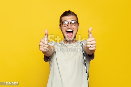 Handsome cheerful man with eyeglasses smiling and showing thumb up gesture with both hands while standing on yellow background and looking at camera.