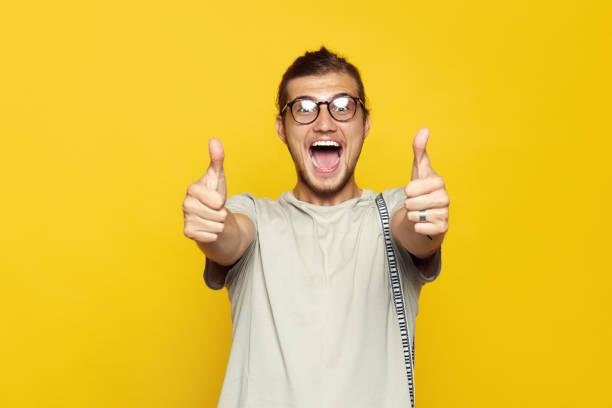 homem caucasiano atrativo que sorri e que mostra o polegar acima do gesto com ambas as mãos sobre o fundo amarelo e a vista da câmera. - excitação - fotografias e filmes do acervo