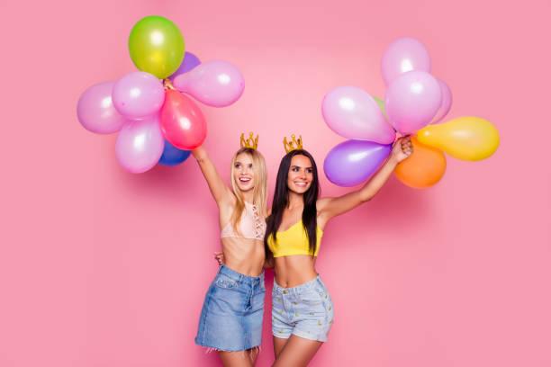 attraktiv, charmant, hübsch, elegant, süß, lächelnd, schlanke mädchen mit goldenen kronen om köpfe umfassend über rosa hintergrund mit bunten luftballons, bereit für geburtstagsparty, frauentag - königin kopfteil stock-fotos und bilder