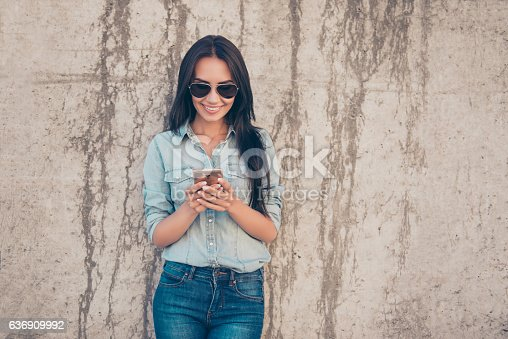 640046924 istock photo Attractive cheerful brunette woman reading sms and using 4g internet 636909992