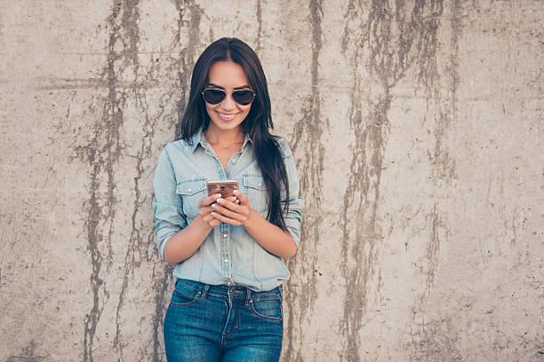 attractive cheerful brunette woman reading sms and using 4g internet - checking stock-fotos und bilder