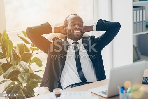 Attractive, cheerful, successful, stylish lawyer enjoying break time, having fun, holding hands behind the head, watching movie on laptop, sitting at desk in sun ray, beam, light, glare
