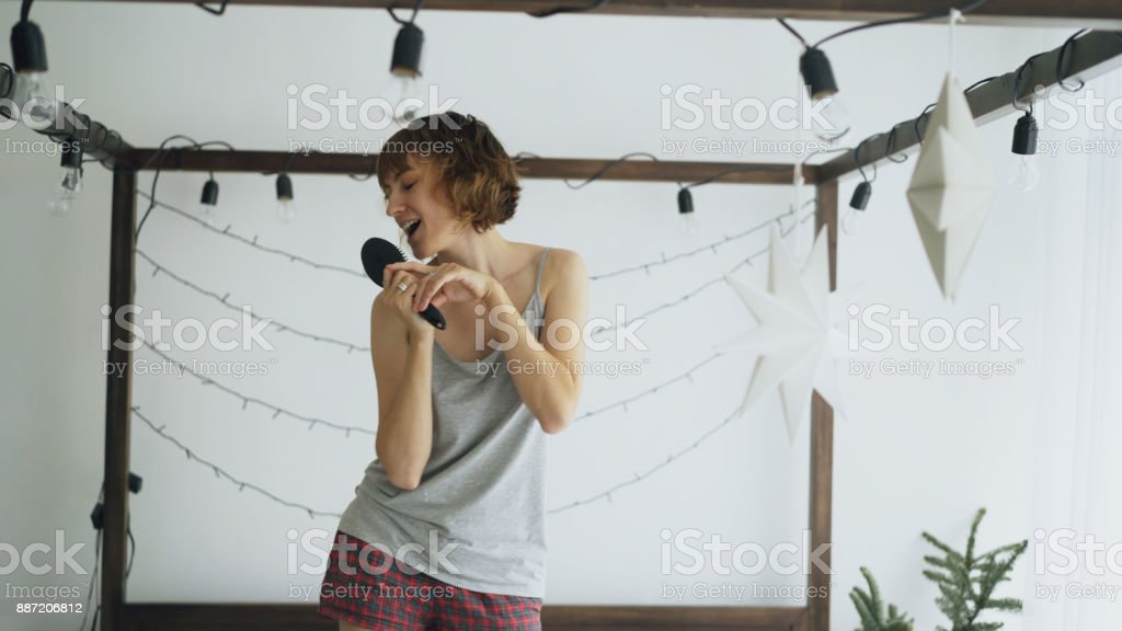 Attractive cheerful woman dancing on bed and singing with comb like microphone at home stock photo