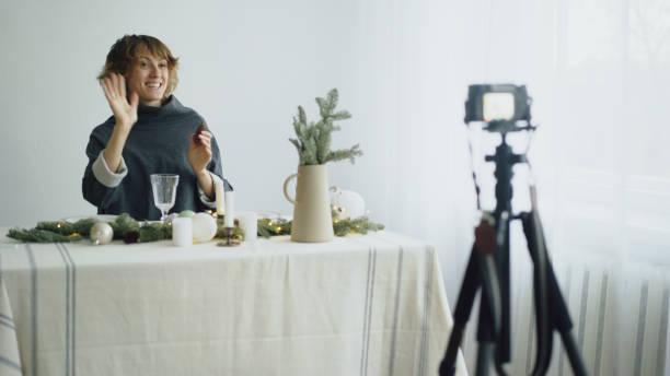 attraktive stets gut gelaunte frau am tisch aufnehmen video-blog über tabellenentwurf einstellung vor der kamera - küche deko blog stock-fotos und bilder