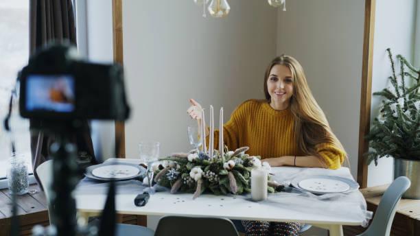 attraktive stets gut gelaunte frau am tisch aufnehmen video-blog über essen dekoration design vor der kamera - küche deko blog stock-fotos und bilder