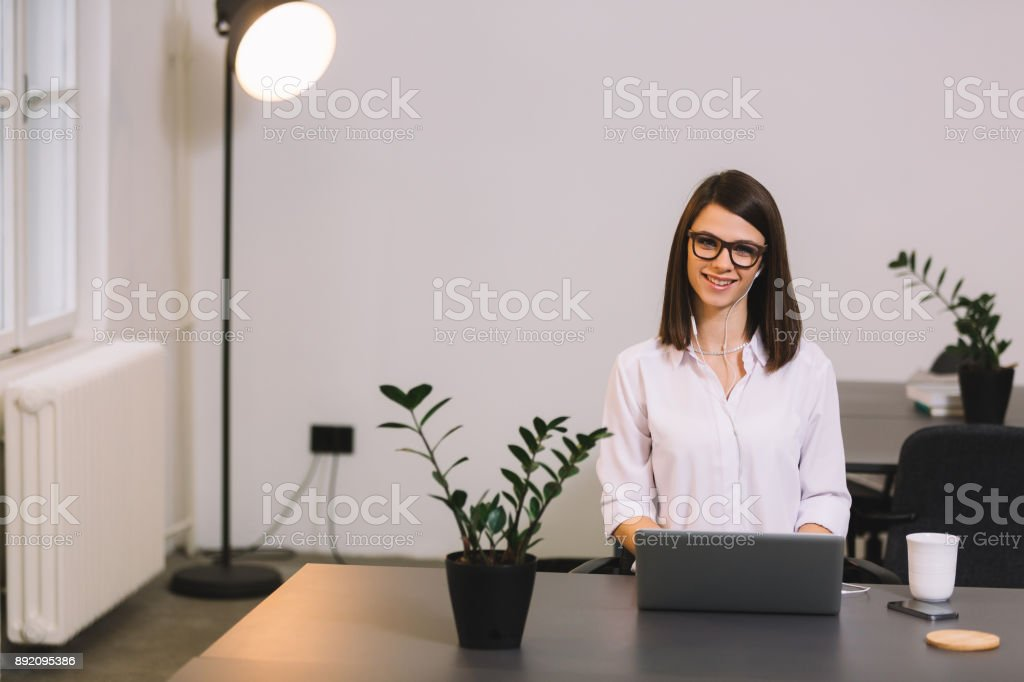 Attractive cheerful young business woman working on laptop and smiling while sitting at her desk in bright office. Front view. stock photo