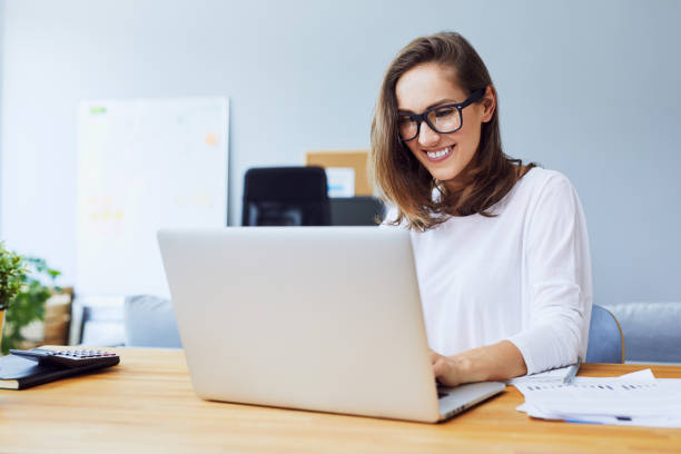 Attractive cheerful young businesswoman working on laptop and smiling while sitting at her desk in bright modern office stock photo