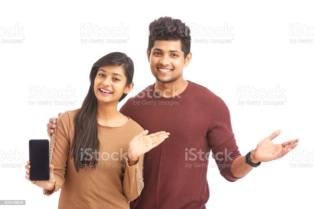 Attractive cheerful young couple holding smart phone and greetings - Stock  image .