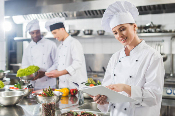 attractive chef reading recipe in recipe book at restaurant kitchen attractive chef reading recipe in recipe book at restaurant kitchen chef stock pictures, royalty-free photos & images