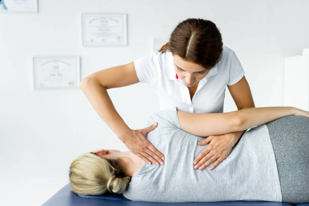 attractive chiropractor touching hand of patient in grey t-shirt attractive chiropractor touching hand of patient in grey t-shirt osteopathy stock pictures, royalty-free photos & images