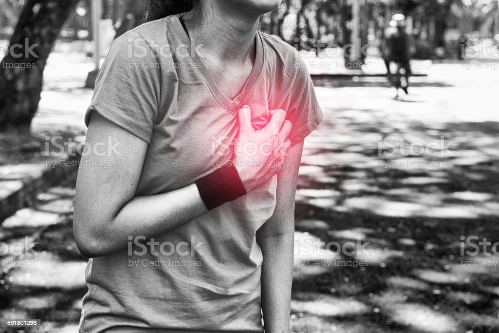 Attractive confidence asian woman runner having a heart attack during a run stock photo