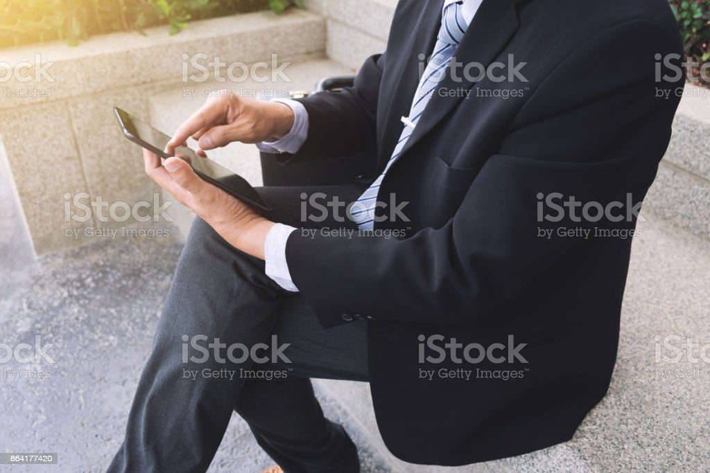Attractive Confident businessman sitting in a black suit and using digital tablet to analyze investment and checking account royalty-free stock photo