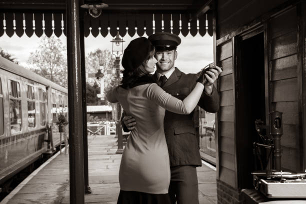 Attractive couple dance on railway station platform with portable record player stock photo