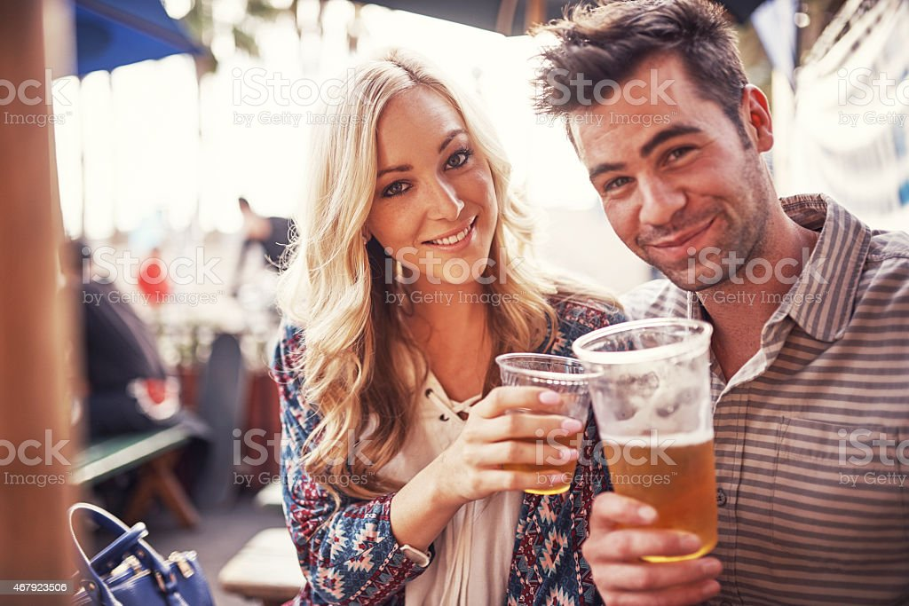 attractive couple drinking beer at outdoor restaurant stock photo