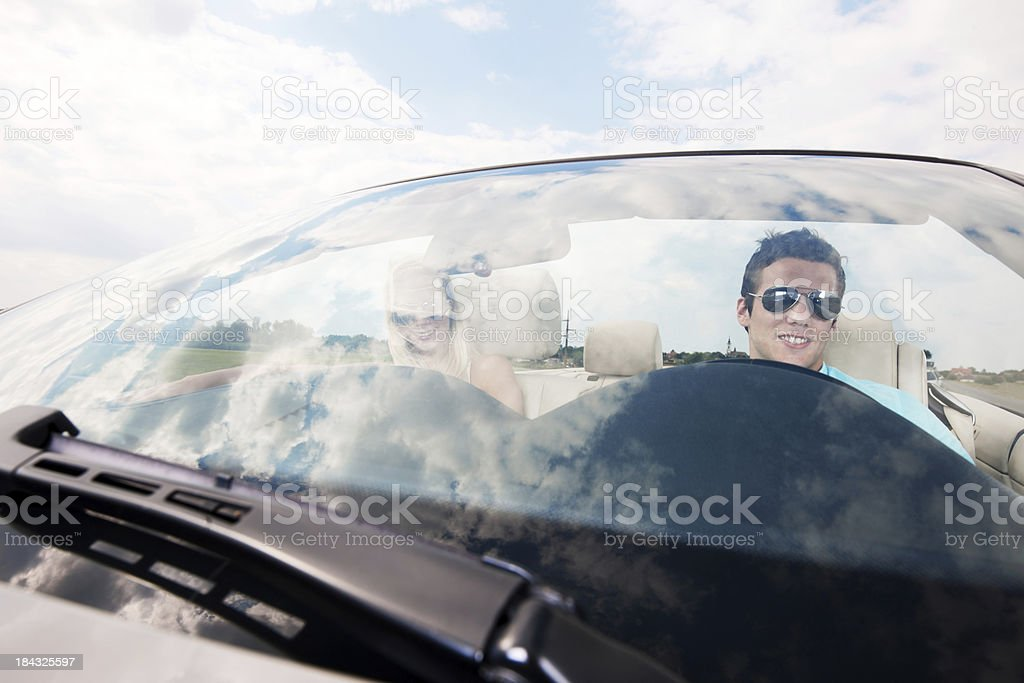 Attractive couple driving in their Convertible car. royalty-free stock photo