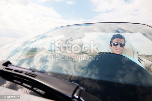 481388538 istock photo Attractive couple driving in their Convertible car. 184325597