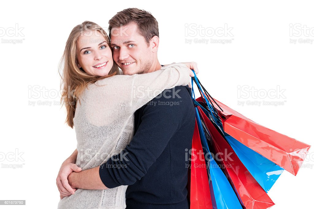 Attractive couple embracing holding bunch of shopping bags photo libre de droits