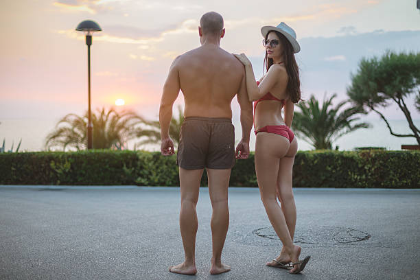attractive couple enjoying sunset on beach attractive  , handsome , pretty , sensual , vacation , young and wild , dating , romance , the view, luxury , summer resort , summer vacation, success g string bikini models stock pictures, royalty-free photos & images