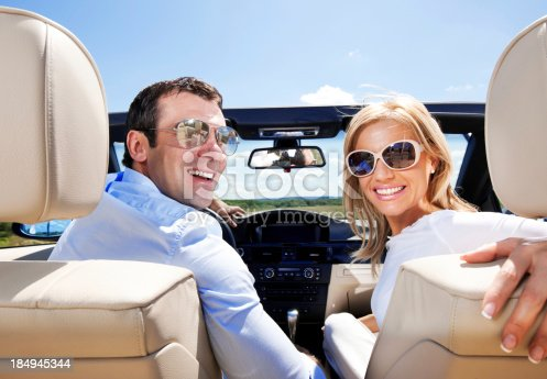 627863858istockphoto Attractive Couple in a Convertible Car 184945344
