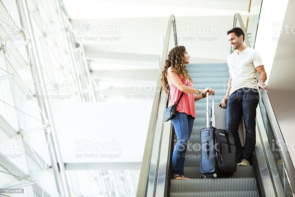Attractive couple in an airport on escalator royalty-free stock photo