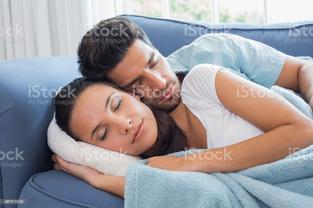 Attractive couple peacefully sleeping on sofa royalty-free stock photo