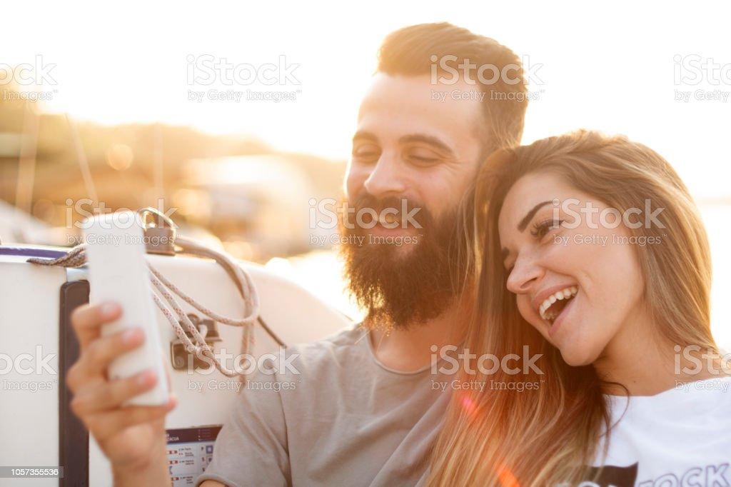 Attraktives Paar entspannt, fotografieren und per Smartphone auf einem Segelboot – Foto