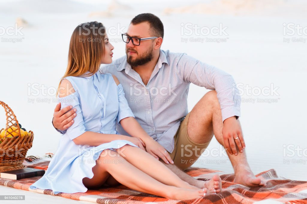 attractive couple sitting together on the white sand beach, looking each other, happy couple enjoying picnic on the beach and have good time on summer vacations, happy couple sitting on a blanket stock photo