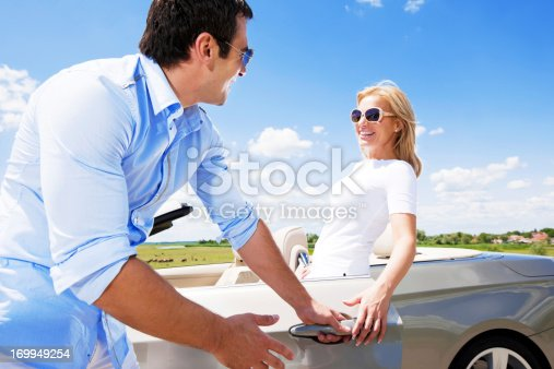 istock Attractive couple standing near Convertible car against the blue 169949254