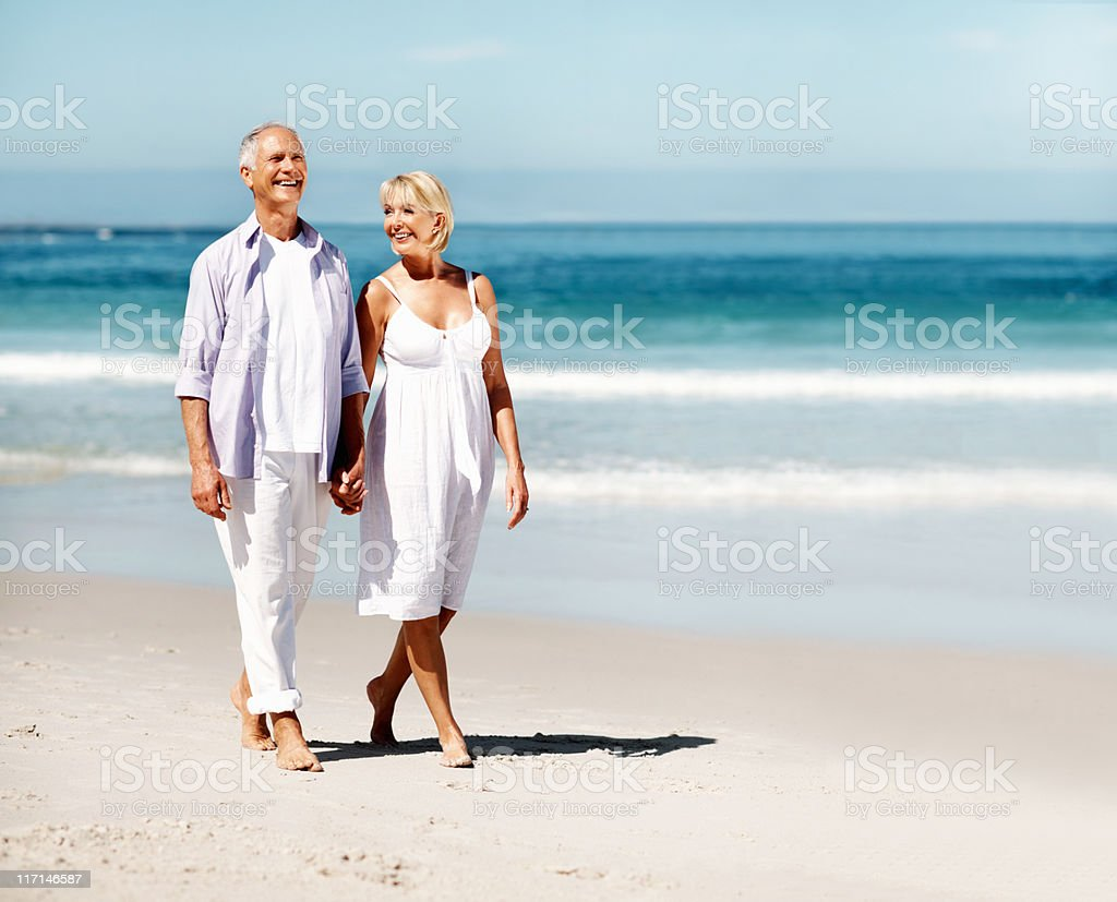 Attractive couple walking on a beach royalty-free stock photo