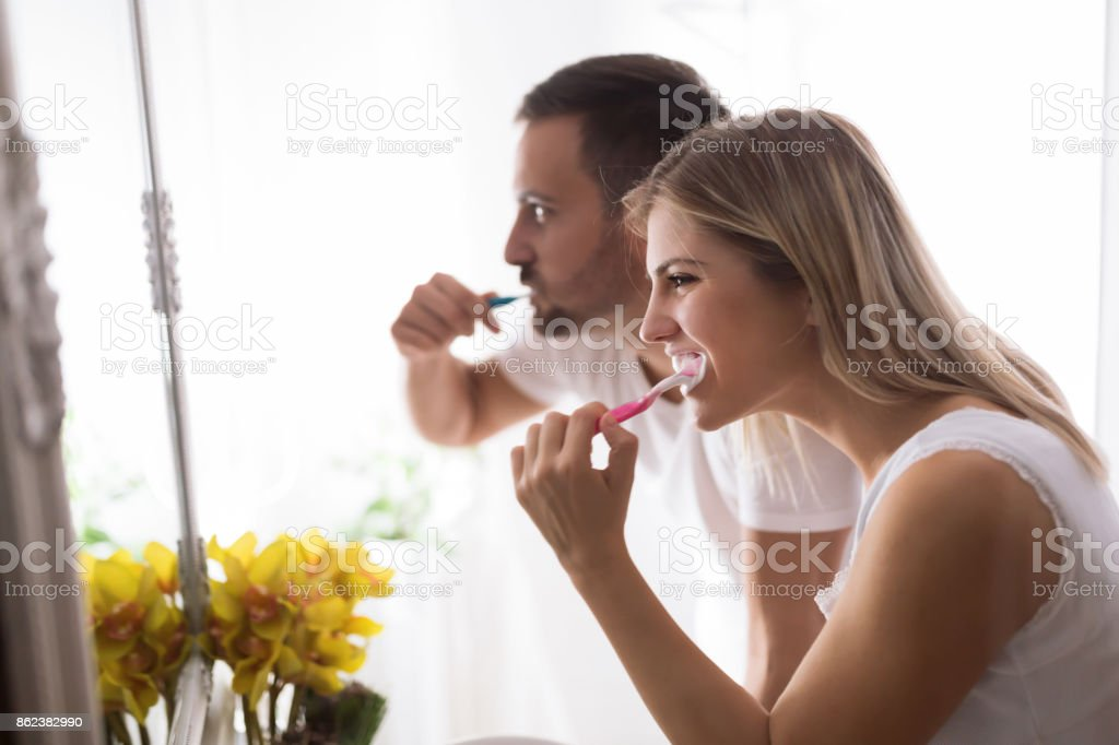 Attractive couple washing teeth in morning together stock photo