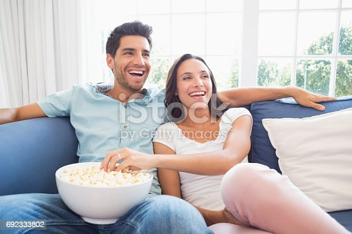 istock Attractive couple watching tv on the couch 692333802