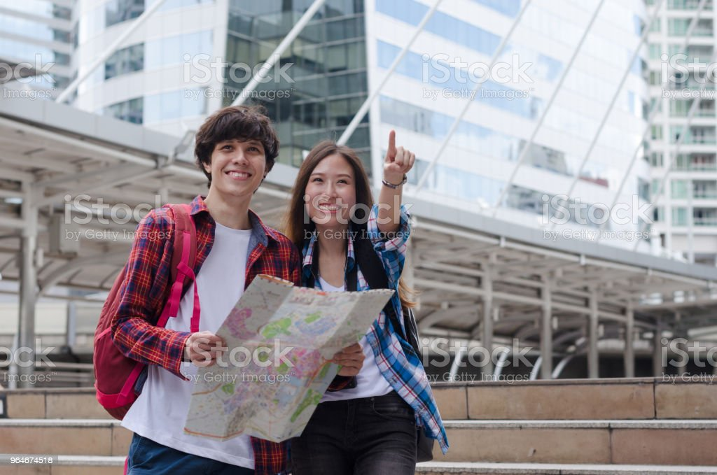 attractive couple young caucasian man and asian woman traveler in modern city Bangkok Thailand with happy and smile. royalty-free stock photo