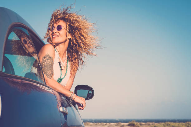 Attractive curly blonde young woman smile and enjoy the wind outside the car - concept of beauty and travel for happy and cheerful caucasian people - alternative lifestyle female feel the freedom and joy stock photo