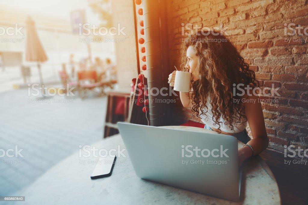 Atractiva morena rizado con laptop en café - foto de stock