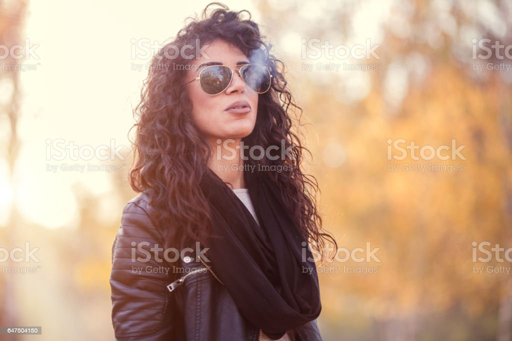 Attractive Curly-haired Girl Smoking Outdoors stock photo