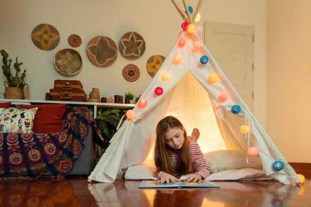 attraktive niedliche mädchen liegen und lesen buch in tipi zelt in ihrem schlafzimmer genießen glückliche zeit. - tipi bett stock-fotos und bilder