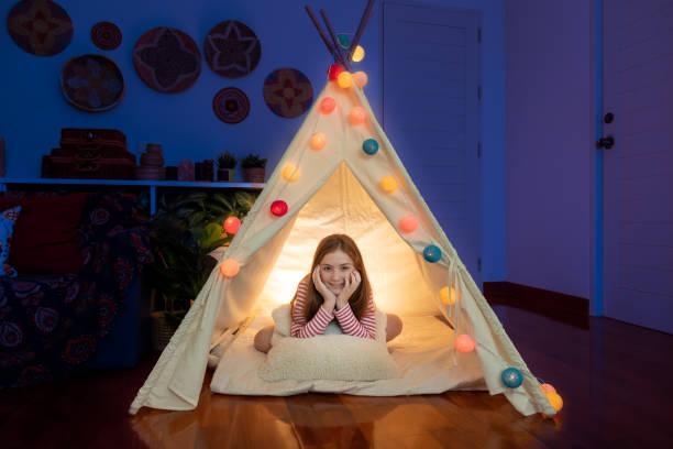 attraktive niedliche mädchen sitzen in tipi-zelt in ihrem schlafzimmer genießen glückliche zeit. - tipi bett stock-fotos und bilder