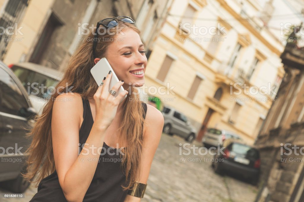 Attractive cute girl talking on her cellphone outdoors. stock photo