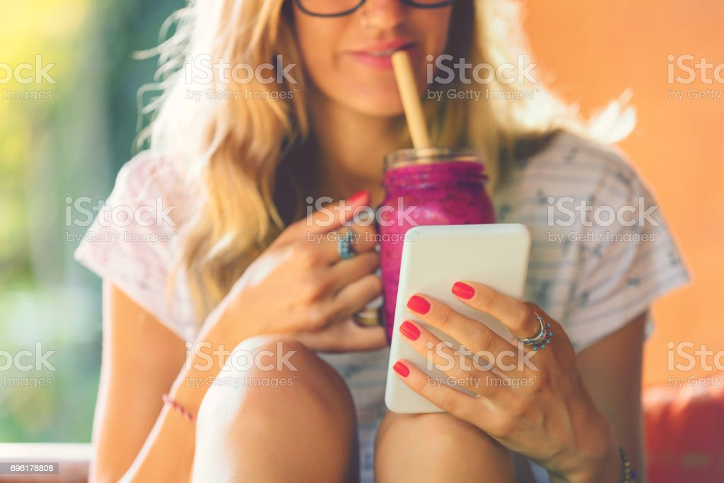 Attractive cute girl using cellphone and drinking smoothie outdoors. stock photo
