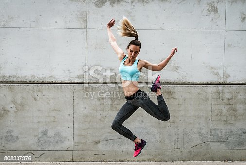 istock Attractive dancer exercising and jumping near the concrete wall 808337376
