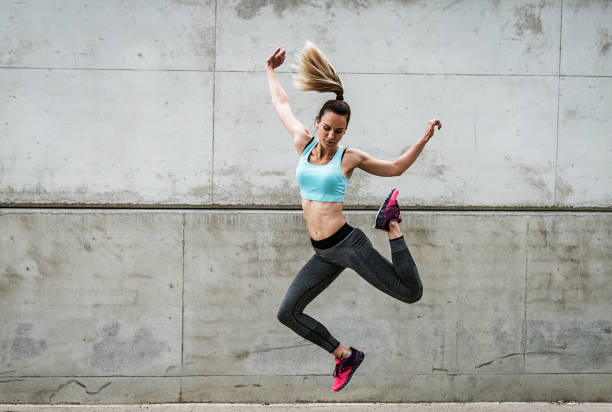 Attractive dancer exercising and jumping near the concrete wall stock photo