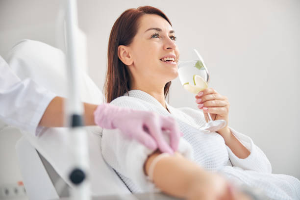 Attractive dark-haired woman smiling during the intravenous therapy stock photo