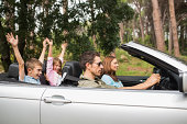 Attractive family in a convertible going on a road trip with the children cheering in the countryside
