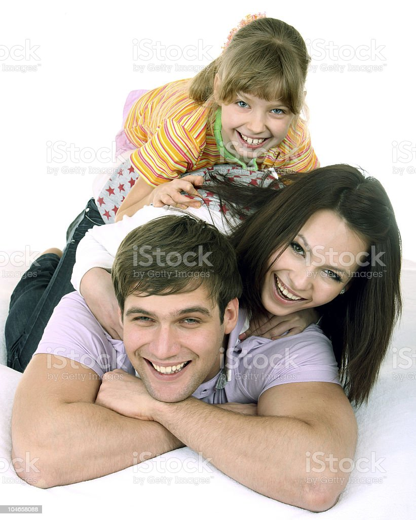 Attractive family on white bed. royalty-free stock photo