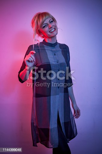 Attractive fashion indoor portrait of beautiful blonde girl posing on purple and blue neon background puling her hair and making painful face