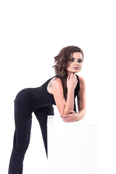 Attractive fashion model wearing black jumpsuit stock photo
