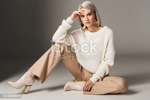 attractive fashionable woman posing in white trendy sweater, beige pants and autumn heels, on grey